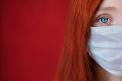 Red-haired girl with a medical mask on a red background Royalty Free Stock Photos