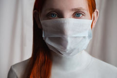 Red-haired girl with a medical mask on a white background Stock Photo