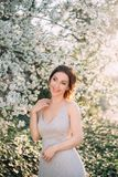 Red-haired girl in a modest, gray dress in rustic style. Portrait of the bride on the background of a blossoming tree royalty free stock photography