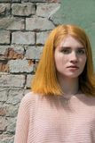 Red-haired girl near the brick wall Royalty Free Stock Photography