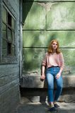 Red-haired girl near the green wall Stock Photo