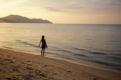 Red Haired Girl on Ocean`s Edge with Arms Out. Young red haired caucasian girl standing on the edge of the ocean with her arms out in Batu Ferringhi, Penang stock image