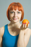 Red-haired girl with orange Stock Photography