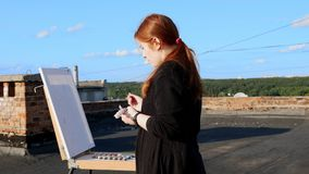 Red-haired girl paints a picture. On the roof. Of the house on a sunny day stock video footage