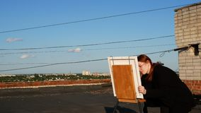 Red-haired girl paints a picture. On the roof. Of the house on a sunny day stock footage