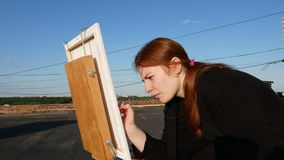 Red-haired girl paints a picture. On the roof. Of the house on a sunny day stock video