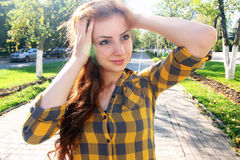 Red-haired girl in a park sunny day outdoor Stock Photography