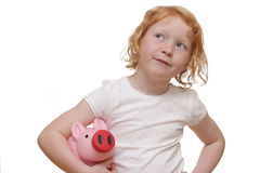 Red-haired girl with piggybank Royalty Free Stock Photo