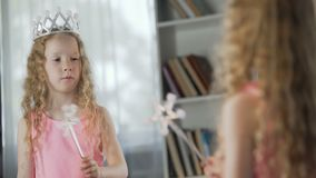Red-haired girl playing role of magic fairy in front of mirror, future actress. Stock footage stock video