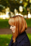 The red-haired girl in profile on a sunny day Stock Photo