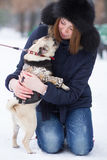 Red haired girl with pug dog. Red haired teen girl playing with funny pug puppy on snow in the park Royalty Free Stock Photo
