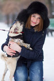 Red haired girl with pug dog. Red haired teen girl playing with funny pug puppy on snow in the park Royalty Free Stock Photos