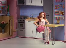 Red-haired girl puppet in the kitchen. Red-haired girl sitting at a toy table in a doll kitchen, doll house concept Stock Photography