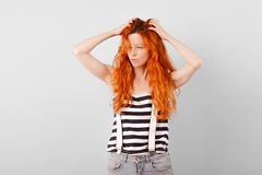 Red-haired girl ran her fingers through her hair and squinted stock image