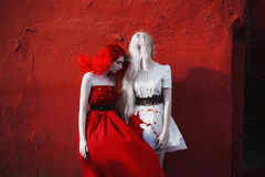 Red-haired girl in a red dress and girl with long white hair in royalty free stock photography