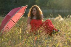 Red- haired girl in a red dress. And with red umbrella in nature Royalty Free Stock Photography
