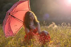 Red- haired girl in a red dress. And with red umbrella in nature Royalty Free Stock Photo