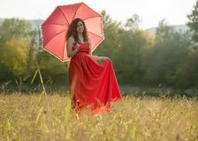 Red- haired girl in a red dress. And with red umbrella in nature Royalty Free Stock Images
