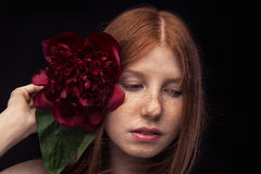 Red-haired girl with red flower Royalty Free Stock Photo