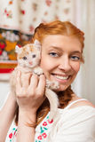 Red-haired girl with a red kitten Royalty Free Stock Photos