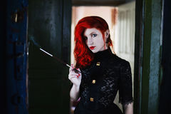 Red-haired girl with red lips in a dark room, a woman holds the mouthpiece with a cigarette in his hand. Pale skin, a door in the background, retro style, noir stock images