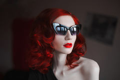 Red-haired girl with red lips and pale skin with dark glasses on a dark background Stock Image