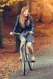 Red haired girl riding on bike in autumnal park stock photos