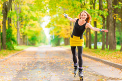 red-haired girl on roller skates rolling Stock Images