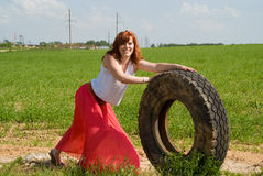 The red-haired girl rolls wheel Royalty Free Stock Photography