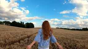Red-haired girl runs through the rye field. Slow motion stock footage