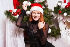 Red-haired girl in the Santa Claus hat. Cheerful red-haired girl in the Santa Claus hat Royalty Free Stock Photos