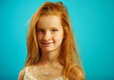 Red haired girl with sincere look on blue background. royalty free stock photo