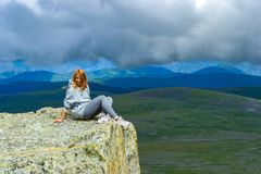 The red-haired girl sits alone on the edge of a cliff in the ray royalty free stock images