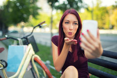 Red-haired girl sitting on the bench make selfie Royalty Free Stock Photo