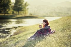 Tirana Artificial lake. Red haired girl sitting at lake shore, drinking hot tea, autumnal portrait, mist covering hills in background Royalty Free Stock Image