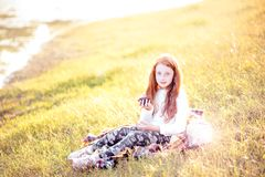 Autumn child portrait. Red haired girl sitting on a lake shore enjoying fresh red apples. Autumn photo mood Stock Photo