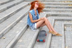 Red haired girl sitting near her scateboard and her hair fly by wind Royalty Free Stock Images