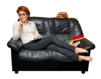 Red-haired girl is sitting on sofa Royalty Free Stock Photography