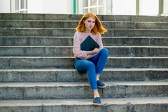 Red-haired girl sitting on the stairs. With a black folder in hands. Redhead Stock Photos