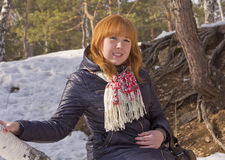 The red-haired girl,sitting on the trunk of a birch. Stock Images