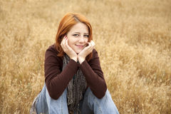 Red-haired girl sitting at yellow autumn grass. Royalty Free Stock Photo