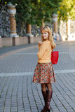 Red-haired girl in a skirt walking in the city on a sunny day Royalty Free Stock Photos