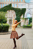 Red-haired girl in a skirt walks and rejoices in the city on a s Stock Photos