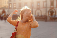 Red-haired girl in a skirt walks and turns his head to the city Stock Photography