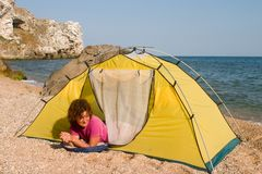 Red-haired girl in sleeping-bag near of tent Stock Photos