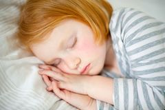 Red-haired girl sleeps with her hands. On her cheek Royalty Free Stock Photos