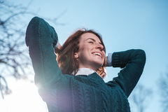 Red-haired girl smiles, enjoying the sun`s rays. She crossed her Royalty Free Stock Images