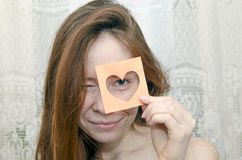 The red-haired girl smiling holding a valentine. The red-haired girl smiling and looking through cut paper valentine Royalty Free Stock Photography
