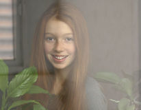 Red-haired girl is smiling. And looking out the window Royalty Free Stock Images