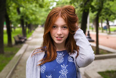 Red-haired girl smiling. With perfect smile and white teeth in a park and looking at camera Royalty Free Stock Image
